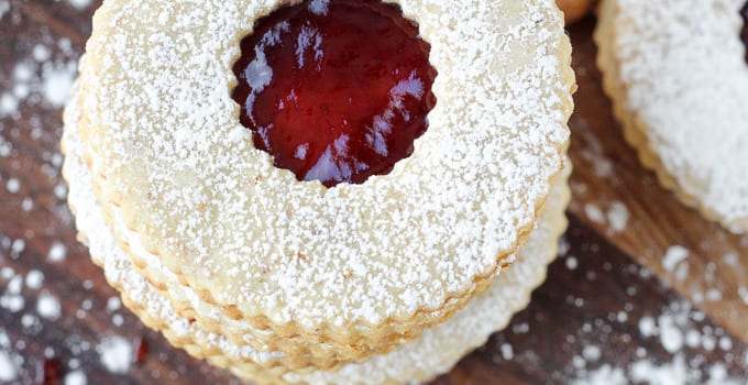 A recipe for the classic Austrian Raspberry Linzer Cookies | A delightful rolled almond cookie filled with raspberry preserves and dusted with powdered sugar! A new Christmas favorite!