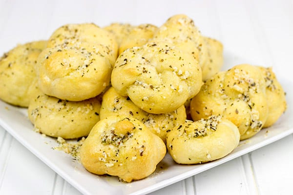 These Parmesan Garlic Knots are an easy, addicting appetizer! Soft homemade pizza dough is brushed with butter and sprinkled with garlic and Parmesan cheese! A perfect recipe for Game Day or any party!