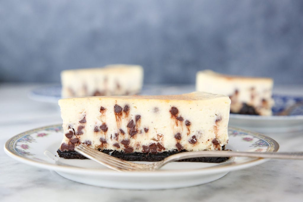 This Chocolate Chip Cheesecake has an easy oreo crust! It is silky and dense, yet surprisingly light! It has the traditional texture and tang of a NY Style Cheesecake!