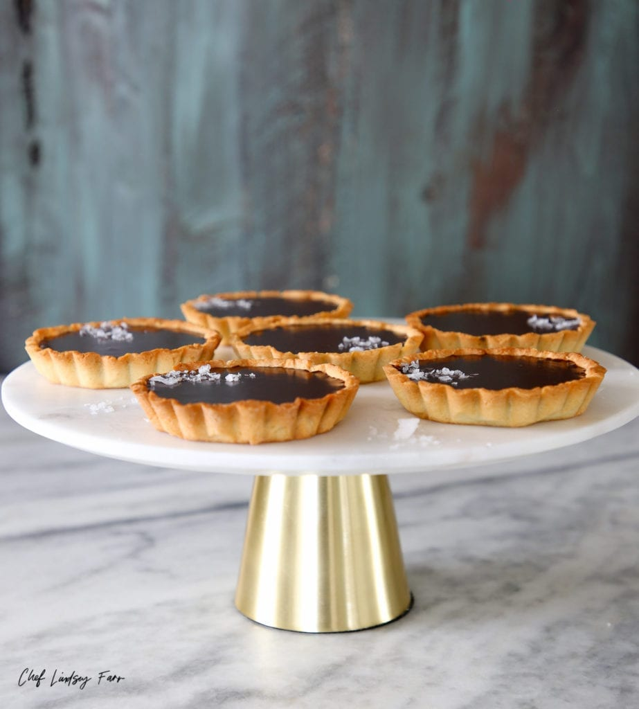 These mini salted chocolate tarts are incredibly easy and perfect for entertaining. The tender almond crust is filled with an irresistibly silky chocolate ganache!